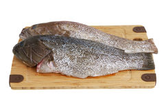 Two scaled  grouper fish on bamboo cutting board Stock Photo