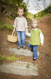Two Scared Children Walking Down Wood Steps with Basket Outside. Royalty Free Stock Photography