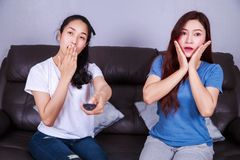 Two scared woman sitting on sofa watching tv Royalty Free Stock Image
