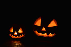 Two Scary faces of Halloween pumpkin. On hardwood Stock Photos