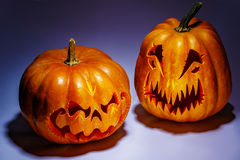 Two scary Halloween pumpkins with shadows on a coloured backgrou Royalty Free Stock Images