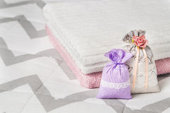 Two scented sachets leaning on two towels on bed. Fragrant lavender pouches for home interior design and storage. Royalty Free Stock Photos