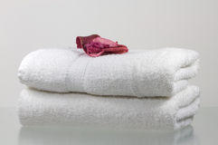 Gentle. Two scented towels adorned with a rose petal Stock Photography