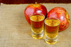 Two schnapps drinks and red apples Stock Photography
