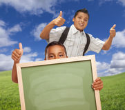Two School Boys Giving Thumbs Up Holding Chalkboard. Hispanic Students with Thumbs Up in Grass Field Holding Blank Chalk Board Stock Photo
