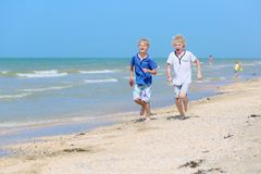 Two school boys running on the beach Stock Photo