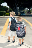 Two school children at crosswalk Royalty Free Stock Photos