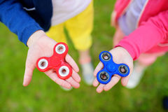 Two school children playing with fidget spinners on the playground. Popular stress-relieving toy for school kids and adults. Royalty Free Stock Image