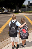 Two school children standing at crosswalk Royalty Free Stock Photo