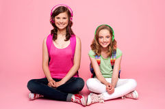 Two school friends sitting on studio floor Royalty Free Stock Photos