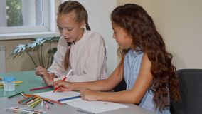 Two school friends talking while drawing together at art class lesson. Two school friends talking and drawing together at art lesson. Cute red haired little girl royalty free stock photos