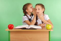 Two school girl sharing secrets  sitting at a desk from book Stock Photos