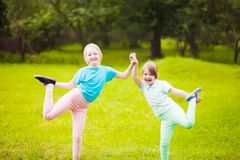 Two school girls doing exercises. Two school girls doing exercises outdoors at the lawn, sunny summer day, sport and lifestyle Royalty Free Stock Photography