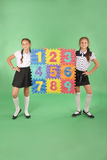Two school girls hold color board with the number Royalty Free Stock Photo