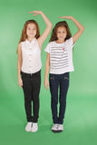 Two school girls hold hands above head and measuring his growth. Isolated on green Royalty Free Stock Image