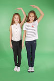Two school girls hold hands above head and measuring his growth Stock Photo