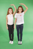 Two school girls hold hands above head and measuring his growth Royalty Free Stock Photography