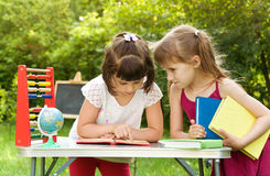 Two school girls are preparing a lesson in nature. They read boo Royalty Free Stock Photos