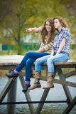 Two school girls sitting on river bridge. Two happy school girls sitting on river bridge on autumn day and looking away Stock Photos