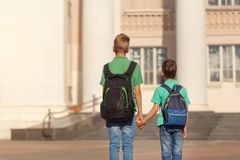 Two school kid boys with backpack on sunny day. Happy children go to school. Back view.  Stock Photo