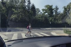 School kids on the pedestrian crossing, view from inside the car royalty free stock image