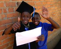 Schoolboys in school uniform and graduation attire holding copys. Two schoolboys one graduation attire and the other in school uniform showing the thumbs up sign royalty free stock photography