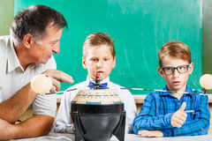 Two schoolboys and their teacher in class. Two schoolboys and their teacher learning solar system in class at the desk against blackboard Royalty Free Stock Image