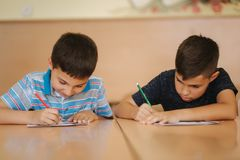 Two schoolboys writing text. Happy children in school. Two schoolboys writing text. Happy children royalty free stock image