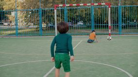 Two schoolchildren play with a soccer ball at the school playground. One student hits the ball, the second hits stock video footage