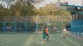 Two schoolchildren throw a ball in a basketball basket of a school playground. Two schoolchildren play ball. They throw balls into the basketball basket, which stock video footage