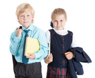 Two schoolchildren in uniform standing with textbooks, isolated white background Stock Images
