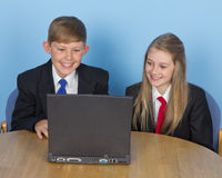 Two schoolchildren, using a computer at home Stock Photos