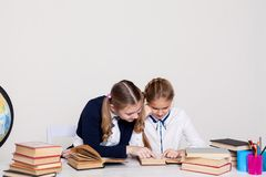 Two schoolgirl girls with books at the school desk