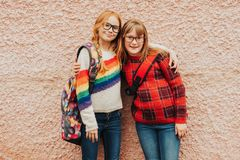 Two schoolgirls with backpacks and glasses royalty free stock image