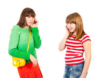Two schoolgirls calling by the mobile phones. Isolated Royalty Free Stock Images
