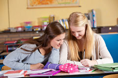 Two schoolgirls in class. Two teenage schoolgirls in classroom having fun together Stock Photos