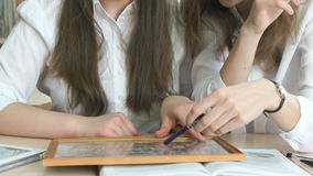 Two schoolgirls looking photo frame with a picture. Two schoolgirls sitting at the desk looking at the photo frame with the picture stock footage