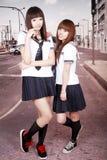 Two schoolgirls outdoors. Two Asian schoolgirls in uniform posing on pedestrian street Royalty Free Stock Photography