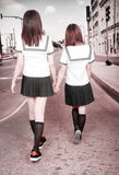 Two schoolgirls outdoors. Royalty Free Stock Image