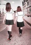 Two schoolgirls outdoors. Two Asian schoolgirls in uniform  walking on pedestrian street Royalty Free Stock Image