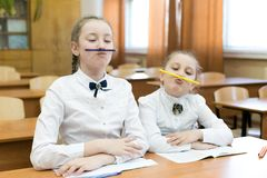 Children indulge in school in the classroom make face mimicry. Two schoolgirls pinch a pencil with their lips to the nose, make a funny facial expression stock images