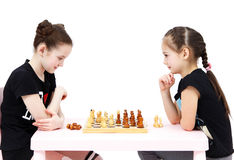 Two schoolgirls play chess on white background Stock Photography