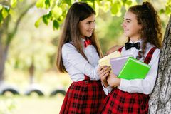 Two schoolgirls in red school checkered uniforms stand in a park near a tree with books