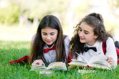 Two schoolgirls in red school uniforms are lying on a green lawn with books