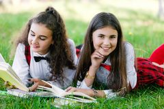 Two schoolgirls in red school uniforms are lying on a green lawn with books stock image