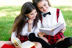 Two schoolgirls in red school uniforms sit on a green lawn with books