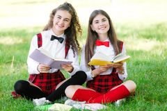Two schoolgirls in school uniforms sit with books in the park. Schoolgirls or students are taught lessons in nature. Two pretty schoolgirls in school uniforms stock photo
