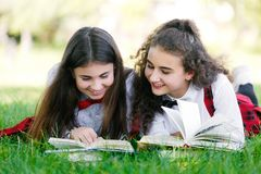 Two schoolgirls in school uniforms sit with books in the park. Schoolgirls or students are taught lessons in nature