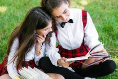 Two schoolgirls in school uniforms sit with books in the park. Schoolgirls or students are taught lessons in nature. Two pretty schoolgirls in school uniforms stock photos