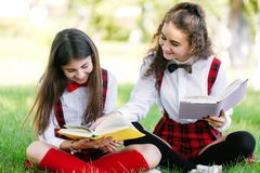 Two schoolgirls in school uniforms sit with books in the park. Schoolgirls or students are taught lessons in nature. Two pretty schoolgirls in school uniforms royalty free stock photo